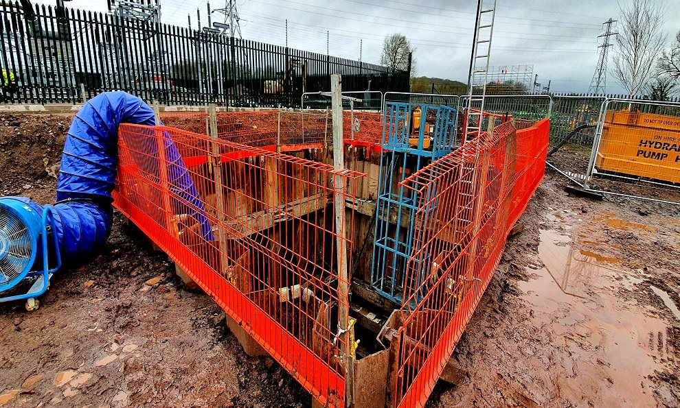 Groundworks support equipment on a large four sided excavation showing sheet piles, fall arret system and edge protection for a basement construction