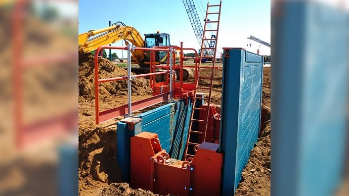A Rolling Strut Box in the ground with barrier protection and ladder to climb in and out of the two sided excavation