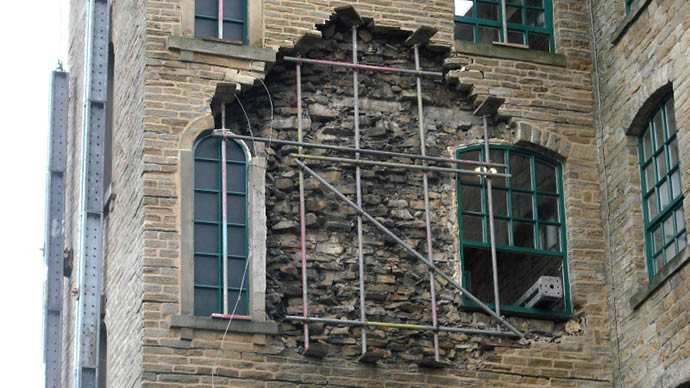 Preventing facade on a crumbling building from falling by proving temporary support with raking shores