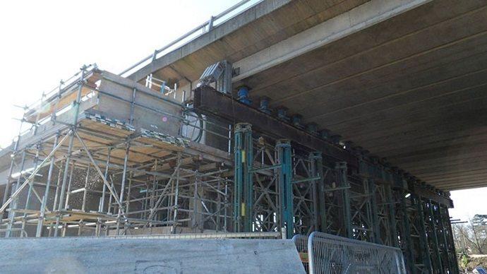 Multiple heavy duty hydraulic jacks lifting a bridge