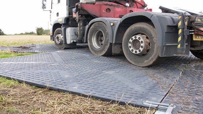 HGV driving on a road mat on grass