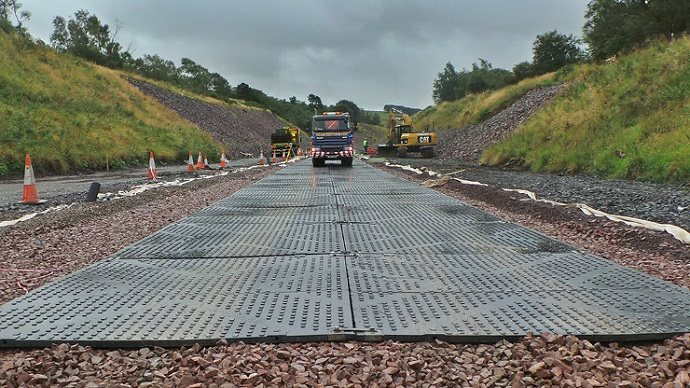 Temporary road mats for ground protection being used by a HGV